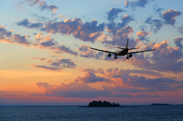 Airplane flying over the sea at sunset