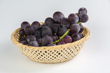 grapes in bamboo basket isolated on white background