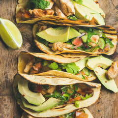 Tacos with grilled chicken, avocado, fresh salsa and limes over rustic wooden background, top view, square crop. Healthy low carb and low fat lunch or food for company. Dieting or weight loss concept