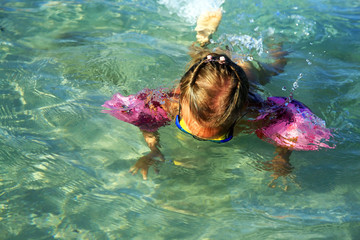 Little girl dives in the clear sea