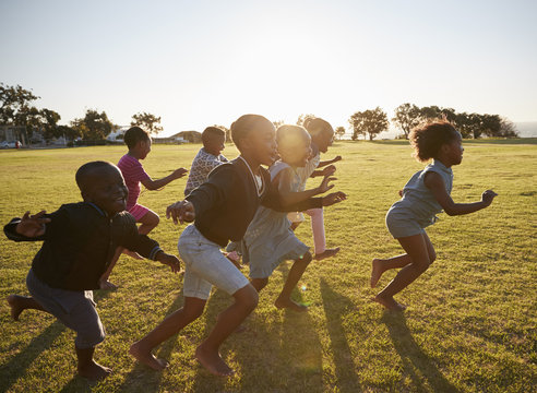 Elementary school kids running together in an open field