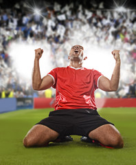 happy and excited football player in red jersey celebrating scoring goal kneeling on grass pitch