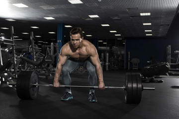 Attractive muscular shirtless athlete preparing to do heavy  dea