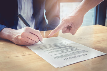 Close up of Agents and business man pointing at sign in contract. Agreement concept.