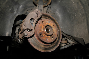 Detail of disk brake on older car showong parts and rust.