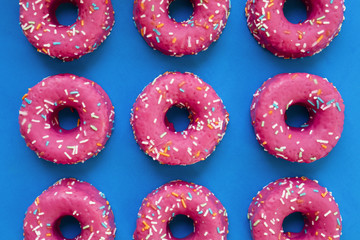 Group of glazed pink donuts on a blue background