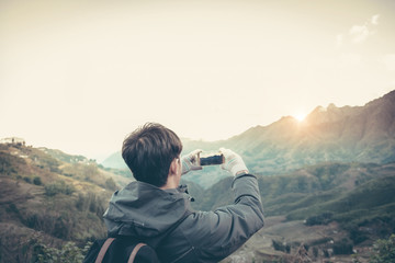 traveler photographing mountain and sun and sky by smartphone.