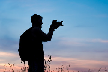 Silhouette of a young who like to travel and photographer, taking pictures of the beautiful moments during the sunset ,sunrise.