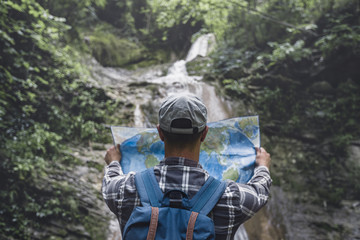 Hiker With Backpack Standing By The Waterfall And Looks At  Map Rear View Holidays And Tourism Concept