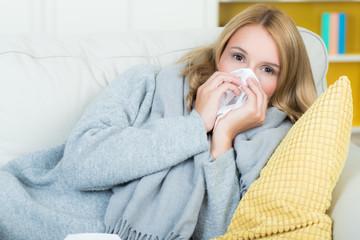erkältete frau mit schnupfen auf dem sofa