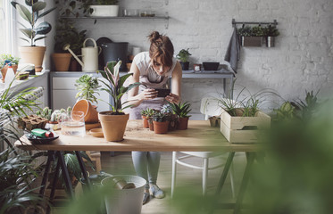 Woman botanist taking photo of her plants using cell phone and standing at her workshop.