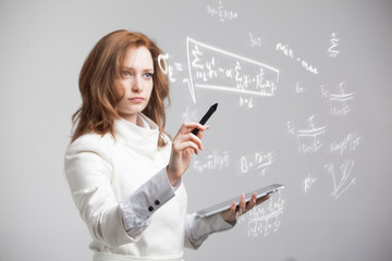 Woman scientist or student working with various high school maths and science formula.