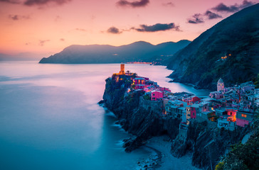 view of famous travel landmark destination Vernazza,small mediterranean old sea town with harbour coast and castle,Cinque terre National Park,Liguria, Italy. Summer colorful sunset with street lights