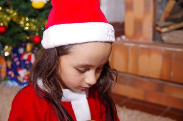 Beautiful sad litle girl wearing a christmas clothes with a christmas tree background with some presents