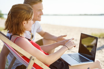 Young couple discussing something on a laptop