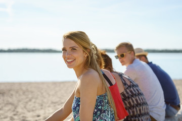 Smiling woman relaxing with friends at the beach