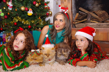 Two beautiful smiling litle girls wearing a christmas clothes, hugging her cats, the curly girl with a red tie in her hair while the brunette girl is wearing a christmas hat with her mom looking