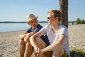 Two young men relaxing on the beach together