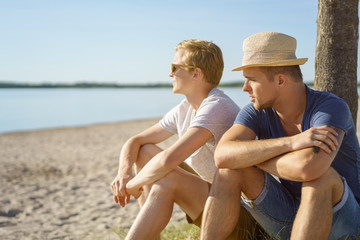 Two young men relaxing together on a beach