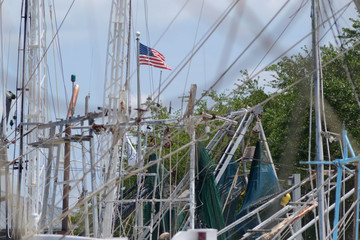 several shrimp boat masts with American flag