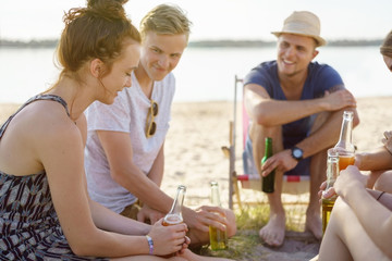 Group of trendy young students relaxing on a beach