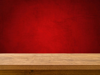 Empty wooden table on red textured background