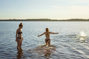 Two young woman going for a swim in the sea