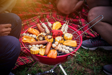 Picnic , BBQ , Camping with Friends Making Foods and Grill Barbecue on Charcoal Stove in the Camp - Travel and Recreation Concept