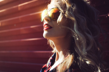 portrait of a girl close-up of a beautiful young sexy blonde in a red plaid shirt and shorts denim in sunglasses smiling and posing on the Sunset hipster