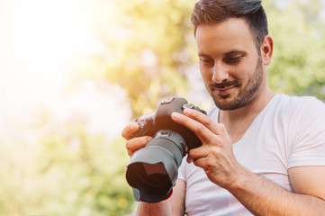 Bearded young man looking at the photos taken with DSLR