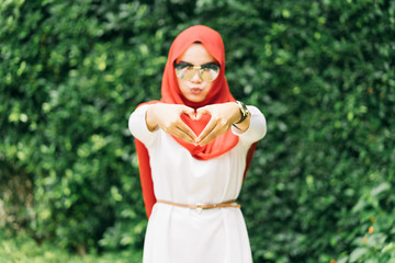Beautiful of happy young muslim woman lift hand showing heart shape.