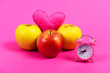 Alarm clock next to three apples and pink heart