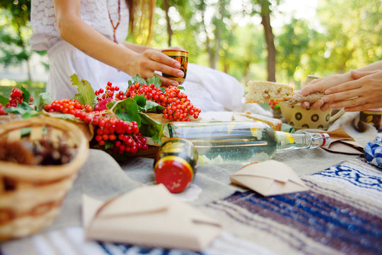 Summer picnic outdoor. Bright and colorful hipster lunch in the park. Female hands cut a piece of pie