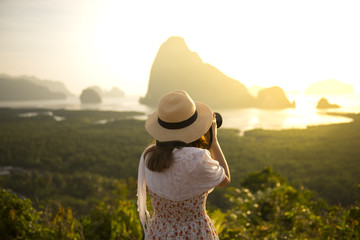 Woman tourist is taking photograph at Samed Nang She point of view in Phang Nga, Thailand during summer time.