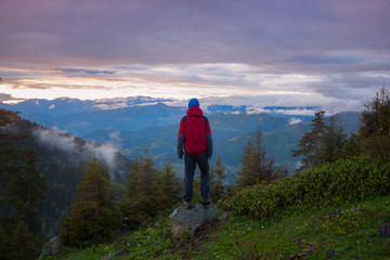 Man traveler admires a colorful sunset in the mountains