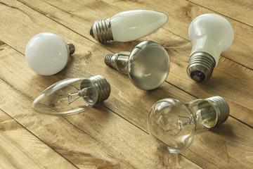 Lamps with different cap lie on a wooden surface