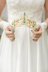 bride's hands hold beautiful crown with green gems