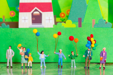 Miniature people family with the balloon using as background happy or celebrity concept.