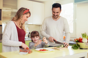 Happy young family preparing lunch in the kitchen