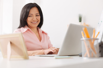 Cheerful asian woman looking at the photo frame