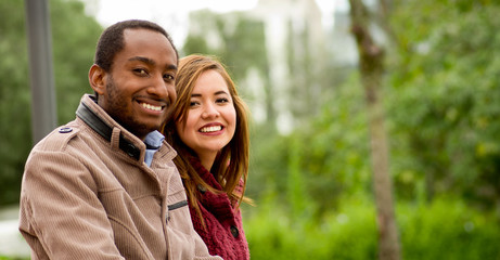 Outdoor portrait of romantic and happy interracial young couple in park