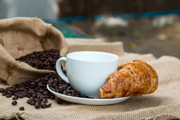Coffee cup with Croissant and bean on the Table