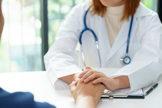 Female doctor holding patient hands for cheerful.