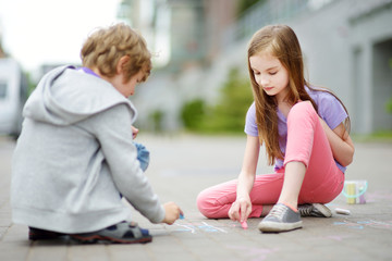 Two happy children drawing with colorful chalks on a sidewalk. Summer activity for small kids.