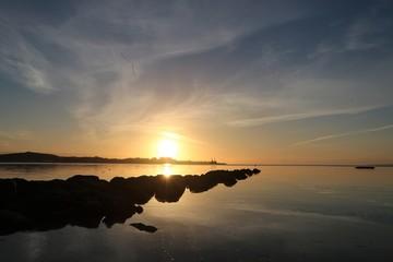 malerischer Sonnenaufgang mit blauem Himmel an einer Buhne an der Ostsee