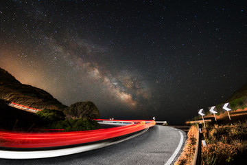 Light trails on the road with the milky way galaxy in background