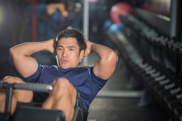 Asian man doing sit-ups at gym.