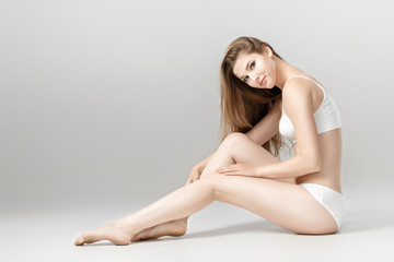 young beautiful  woman with perfect body in white underwear sitting on floor. Smooth skin after depilation