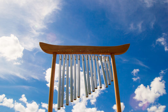 Wind musical chimes on the background of blue summer sky.