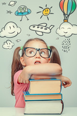 beautiful cute little girl imagining while leaning on thick books